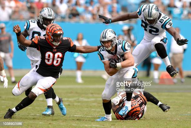 Carolina Panthers running back Christian McCaffrey center breaks free for yardage as Cincinnati Bengals defensive end Carlos Dunlap left looks to...