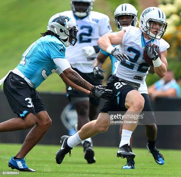 Carolina Panthers running back Christian McCaffrey right breaks free of cornerback Zach Sanchez left on a run during the team's second day of...