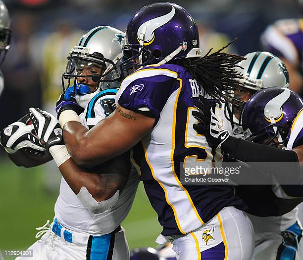Carolina Panthers running back DeAngelo Williams is stopped by Minnesota Vikings linebacker EJ Henderson and safety Darren Sharper on a run to the...