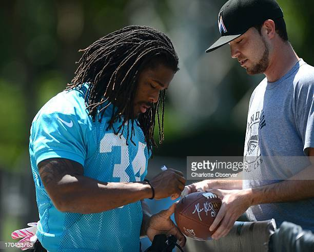 Carolina Panthers running back DeAngelo Williams, left, stops to sign an autograph for a fan prior to mini-camp practice, Thursday, June 13 in...
