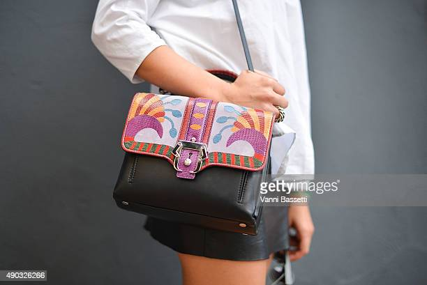 Carolina Stigliano poses with a Paula Cademartori bag before the MSGM show during the Milan Fashion Week Spring/Summer 16 on September 27 2015 in...