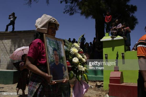 Carolina Tomas holds the photograph of Adan Coronado during the burial on March 14, 2021 in Comitancillo, Guatemala. 19 shot and charred bodies were...