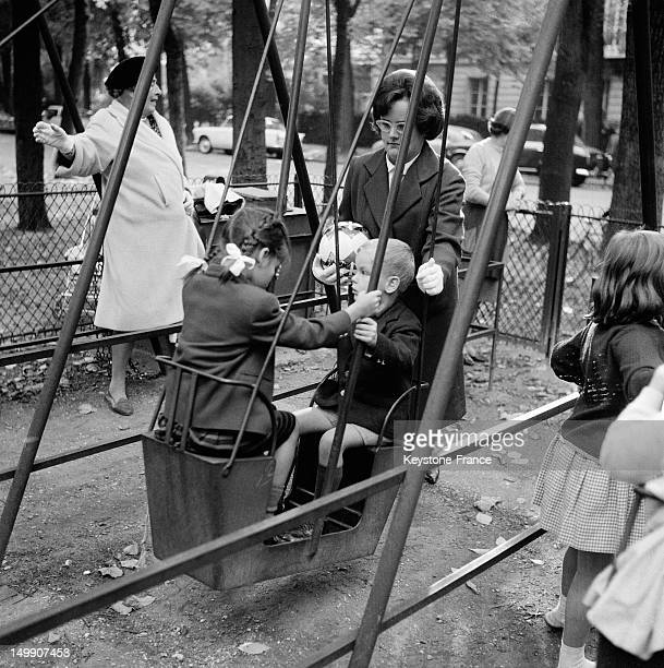 Caroline and Albert on a swing with their nanny at kindergarten on October 6 1962 in Paris France