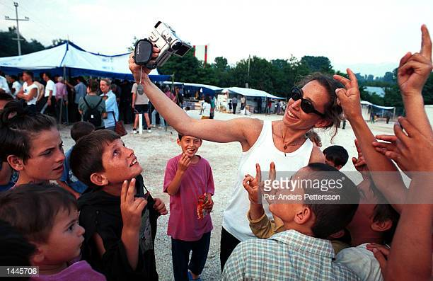 Caroline Barron, an American movie producer uses her video camera at a camp for Kosovar refugees June 15, 1999 in Cegrane, 50 miles outside Skopje,...