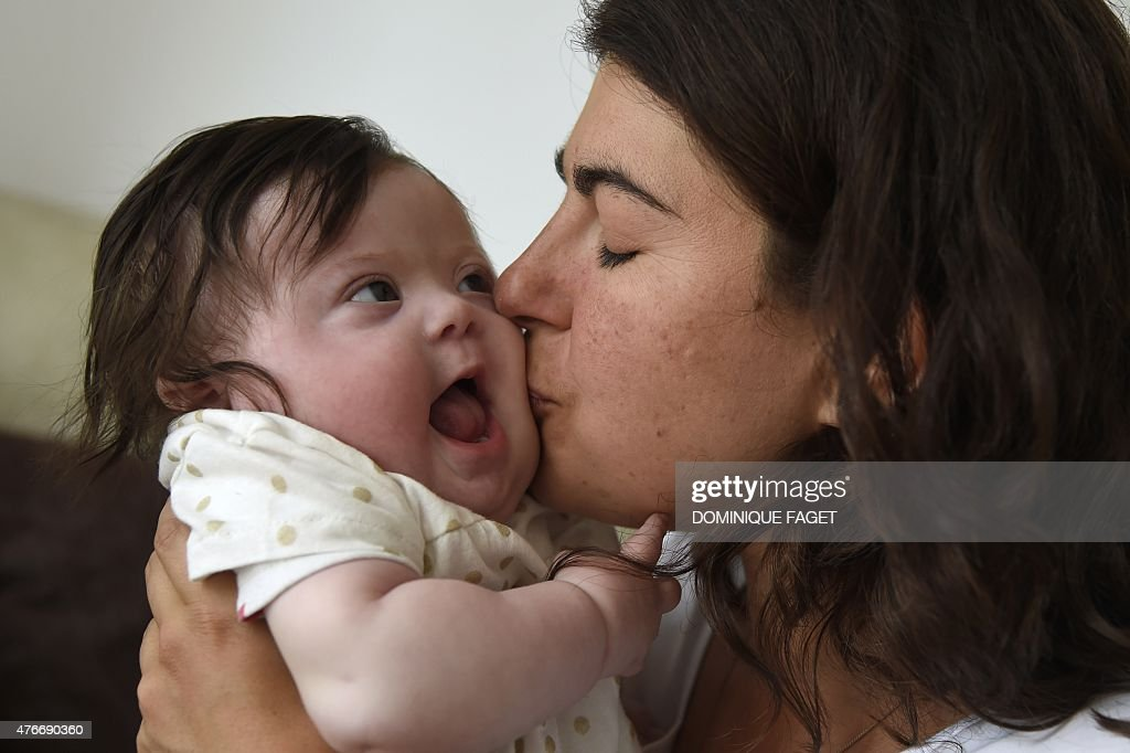 Caroline Boudet kisses her daughter Louise's cheek as they pose in...
