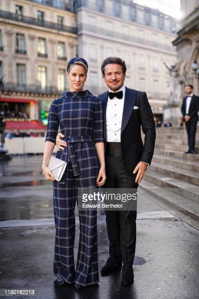 A guest wears a navy blue windowpane check jumpsuit with flare pants a matching headband a white openwork clutch bejewelled navy blue lace pointy...