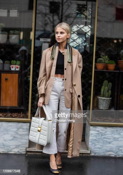 Caroline Caro Daur is seen weairng camel trench coat, blazer, white pants, bag outside Sacai during Paris Fashion Week - Womenswear Fall/Winter...