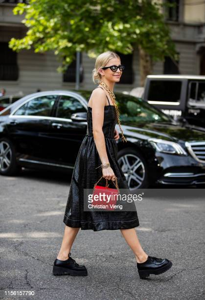 Caroline Caro Daur is seen wearing black dress red bag golden necklace outside Marni during the Milan Men's Fashion Week Spring/Summer 2020 on June...