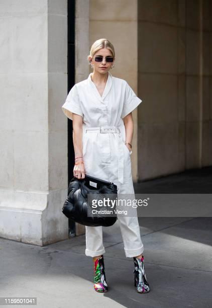 Caroline Caro Daur is seen wearing black Margiela bag white overall outside Schiaparelli during Paris Fashion Week Haute Couture Fall/Winter...