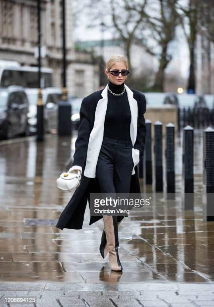 "Caroline ""Caro"" Daur is seen wearing black white two tone coat, turtleneck, mini bag, beige black two tone boots outside Victoria Beckham during..."
