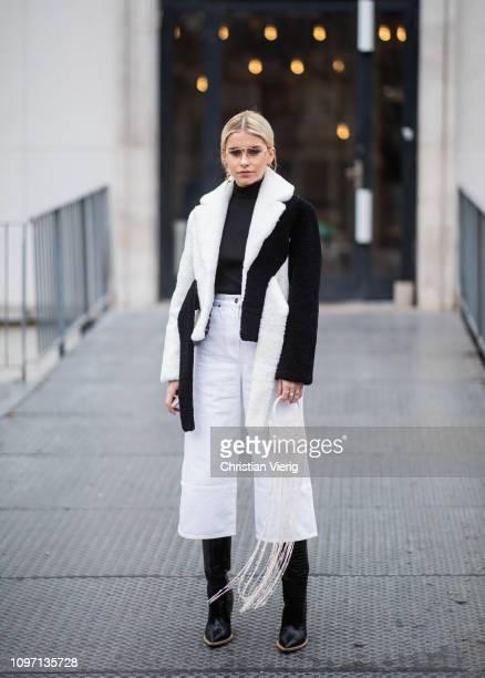Caroline Caro Daur is seen wearing black white two tone jacket, mini bag with fringes, white cropped pants outside Jacquemus during Paris Fashion...