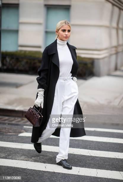 Caroline 'Caro' Daur is seen wearing gloves turtleneck white pants black coat outside Ralph Lauren during New York Fashion Week Autumn Winter 2019 on...
