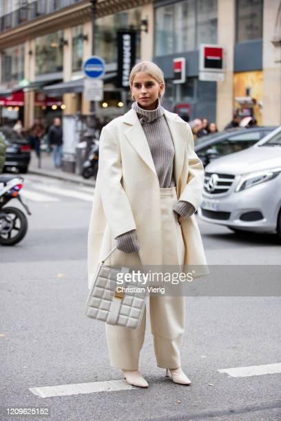 Caroline Caro Daur is seen wearing grey turtleneck knit, creme white coat, wide leg pants, checkered bag outside Nina Ricci during Paris Fashion Week...