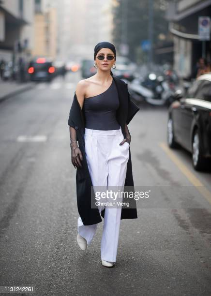 Caroline Caro Daur is seen wearing ripped off top head scarf white pants black coat sheer gloves outside Max Mara on Day 2 Milan Fashion Week...