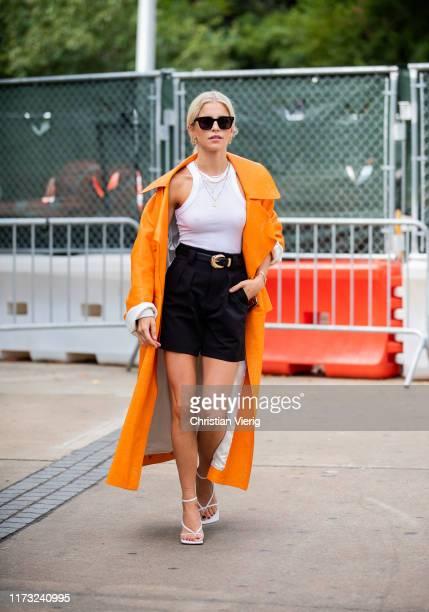 Caroline Caro Daur is seen wearing shorts, orange coat outside Tory Burch during New York Fashion Week September 2019 on September 08, 2019 in New...
