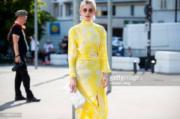 "Caroline ""Caro"" Daur is seen wearing yellow dress with print, Margiela clutch outside Acne during Paris Fashion Week - Haute Couture Fall/Winter..."