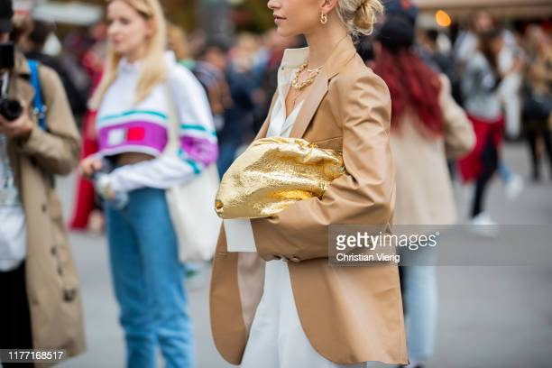 Caroline Caro Daur seen wearing beige jacket, white high waist pants, sandals, golden Bottega Veneta pouch outside Rochas during Paris Fashion Week...