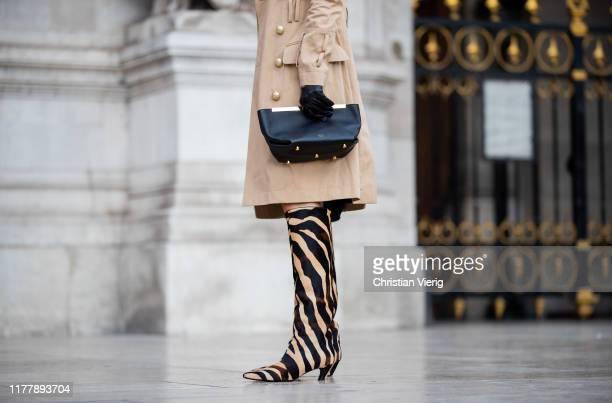 Caroline Caro Daur seen wearing boots with animal print gloves Celine bag trench coat outside Balmain during Paris Fashion Week Womenswear Spring...