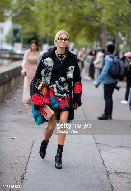 Caroline Caro Daur seen wearing jacket and dress with graphic print, Valentino bag outside Valentino during Paris Fashion Week Womenswear Spring...