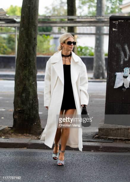 Caroline Caro Daur seen wearing white coat with slit, black dress, black bag outside Alessandra Rich during Paris Fashion Week Womenswear Spring...