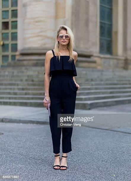 Caroline Caro Daur wearing Dior sunglasses a navy Topshop jumpsuit heels and a pink Marina Hoermanseder clutch on May 29 2016 in Berlin Germany