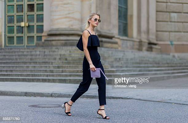 Caroline Caro Daur wearing Dior sunglasses a navy Topshop jumpsuit heels and a pink Marina Hoermanseder clutch on May 29 2016 in Berlin Germany