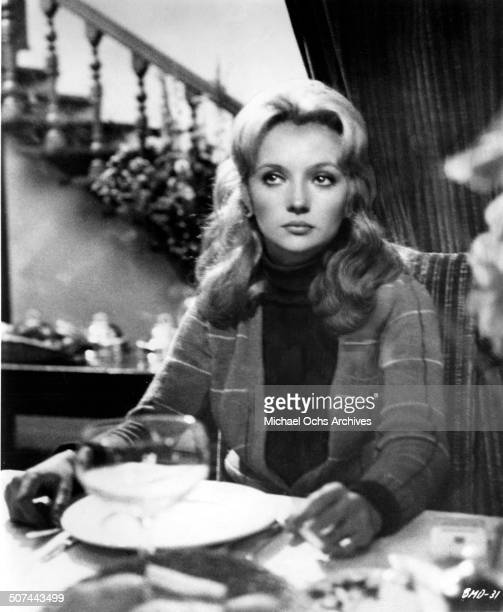 Caroline Cellier at a dinner table in a scene from the movie This Man Must Die circa 1969
