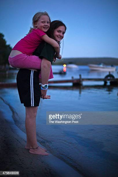 Caroline Cole from Massachusetts holds her cousin Frances Byrne from NY at days end outside the cottages at Bear Spring Camps It's an oldfashioned...