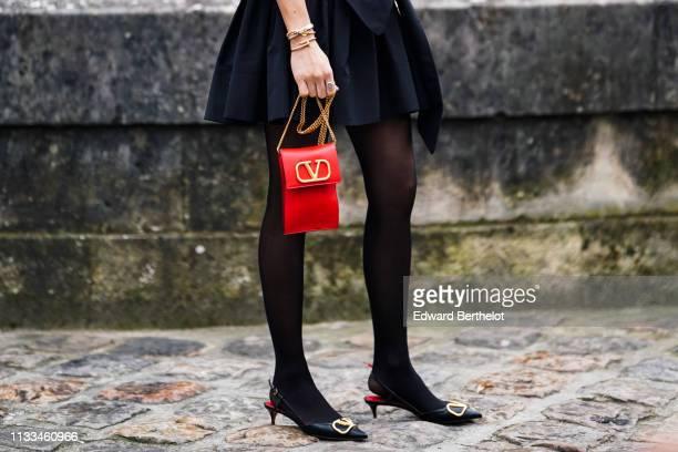 Caroline Daur a black gathered dress a red Valentino bag black Valentino pointy kitten heeled slingback pumps black tights outside Valentino during...