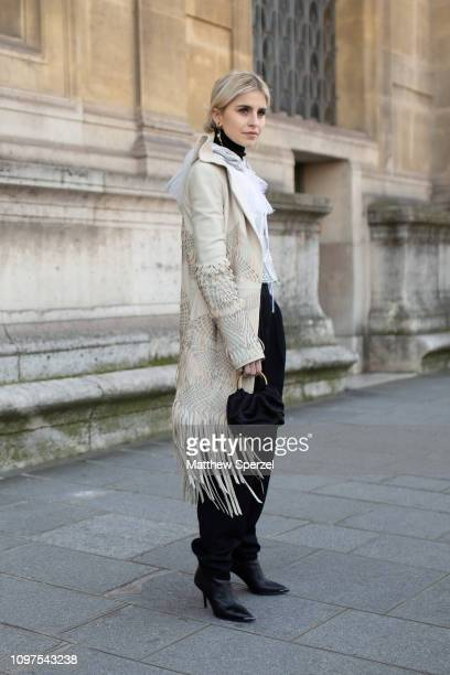 Caroline Daur is seen on the street attending Iris van Herpen during Paris Haute Couture Fashion Week wearing taupe coat with white sheer shirt and...