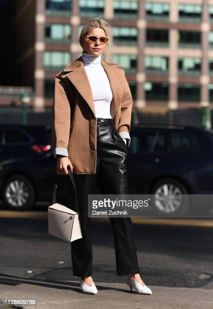 Caroline Daur is seen wearing a brown coat white sweater black leather pants and white bag outside the Self Portrait show during New York Fashion...