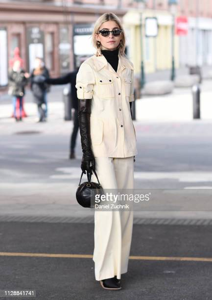 Caroline Daur is seen wearing a cream top and pants with a black purse outside the Tory Burch show during New York Fashion Week Fall/Winter 2019 on...