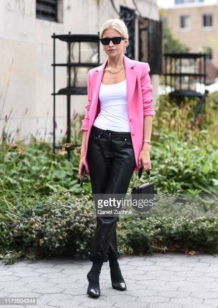 Caroline Daur is seen wearing a pink jacket, white top, black leather pants and black sunglasses outside the Carolina Herrera show during New York...