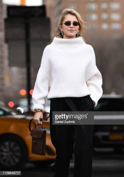 Caroline Daur is seen wearing a white sweater black pants and brown bag outside the Boss show during New York Fashion Week Fall/Winter 2019 on...