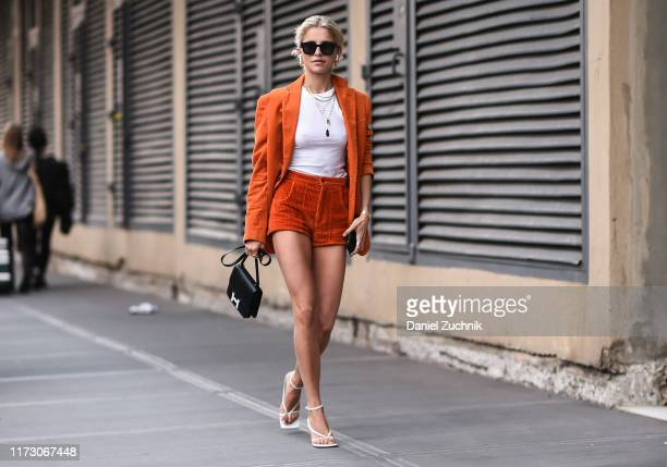 Caroline Daur is seen wearing an orange jacket, white top and orange shorts and black bag outside the R13 show during New York Fashion Week S/S20 on...