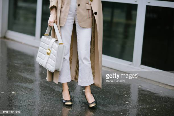 Caroline Daur poses wearing a Sacai trench coat and a Bottega Veneta bag after the Sacai show during Paris Fashion Week Womenswear Fall/Winter...