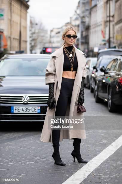 Caroline Daur, wearing a black crop top, black pants, long cream coat, black gloves black boots and a purple little bag, is seen outside Elie Saab on...