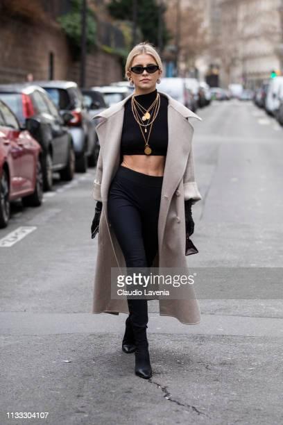 Caroline Daur wearing a black crop top black pants long cream coat black gloves black boots and a purple little bag is seen outside Elie Saab on Day...