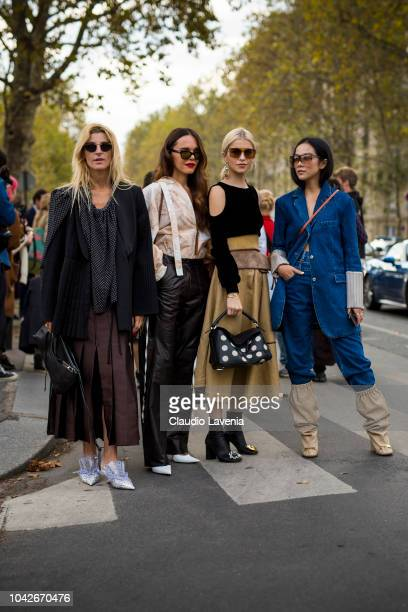 Caroline Daur wearing a black sweater beige midi skirt black boots and Loewe bag Ada Kokosar wearing black blazer brown midi skirt and silver heels...