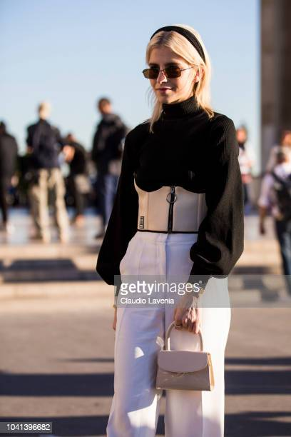 Caroline Daur wearing a black turtleneck sweater beige corset white trousers and mini beige bag is seen after the Rochas show on September 26 2018 in...