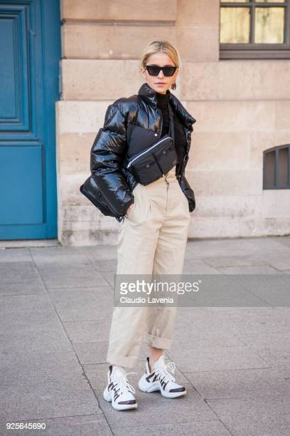 Caroline Daur, wearing a black winter coat, Louis Vuitton sneakers and beige pants, is seen in the streets of Paris after the Lanvin show during...