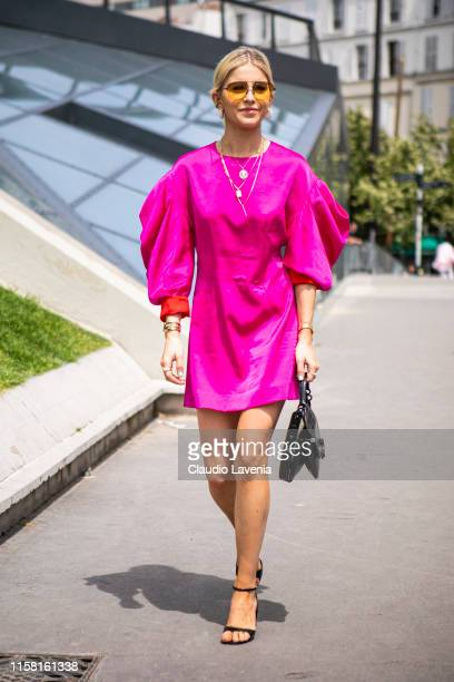 Caroline Daur wearing a hot pink dress black sandals and black Kenzo bag is seen outside Kenzo fashion show on Day 6 during the Paris Fashion Week...