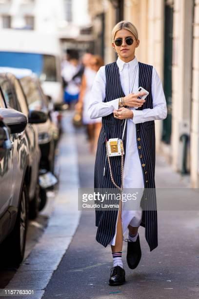 Caroline Daur, wearing a long white shirt dress, blue striped long vest, white mini bag and black shoes, is seen outside Thom Browne fashion show on...