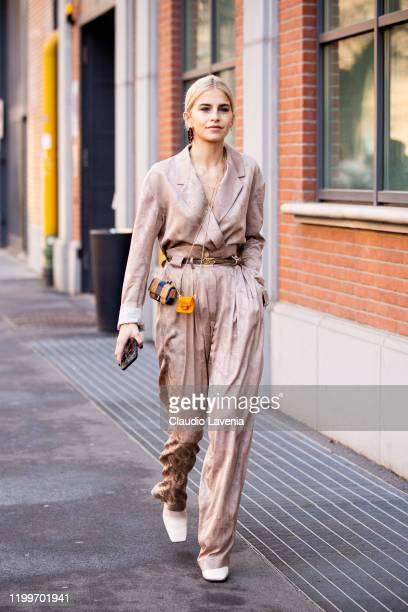 Caroline Daur, wearing a nude decorated shirt with matching pants, Fendi belt, white boots and Fendi mini crossbody bags, is seen outside the Fendi...