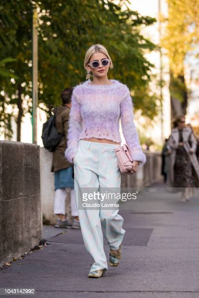 Caroline Daur, wearing a pink sweater, light blue and light pink polka dot pants, pink bag and printed shoes, is seen before the Haider Ackermann...