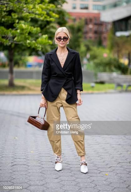 Caroline Daur wearing beige pants black blazer brown bag white heels is seen outside SelfPortrait during New York Fashion Week Spring/Summer 2019 on...