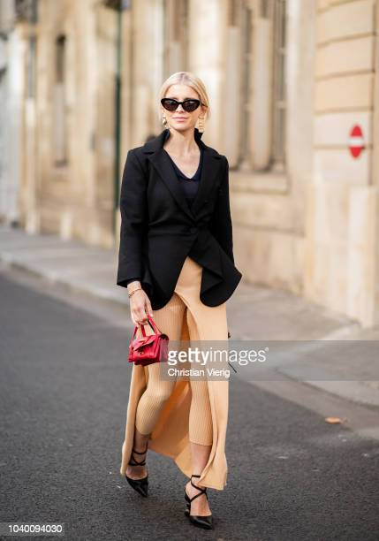 Caroline Daur wearing beige pants red Jacquemus bag black blazer bag is seen outside Jacquemus during Paris Fashion Week Womenswear Spring/Summer...