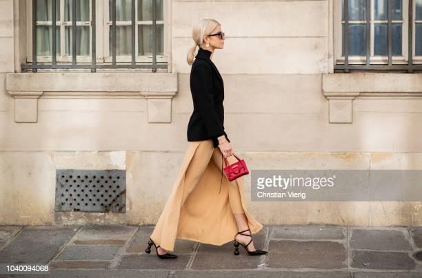 Caroline Daur wearing beige pants red Jacquemus bag black blazer bag is seen outside Jacquemus during Paris Fashion Week Womenswear Spring/Summer...