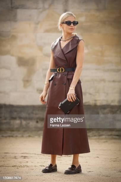 Caroline Daur wearing Dior leather dress, Dior belt, Dior clutch and Dior shoes outside the Dior show as part of the Paris Fashion Week Womenswear...