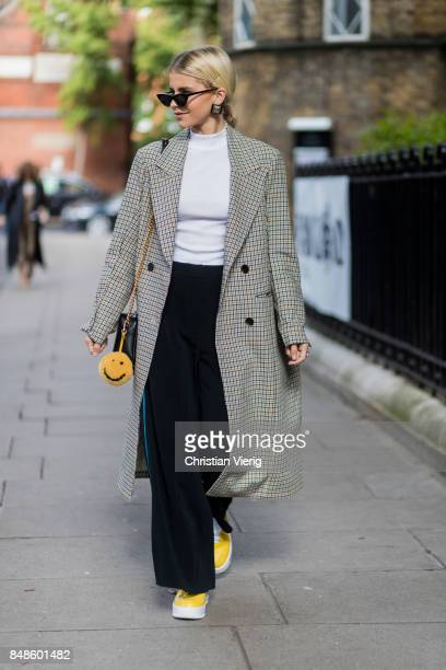 Caroline Daur wearing flared pants checked coat outside Anya Hindmarch during London Fashion Week September 2017 on September 17 2017 in London...